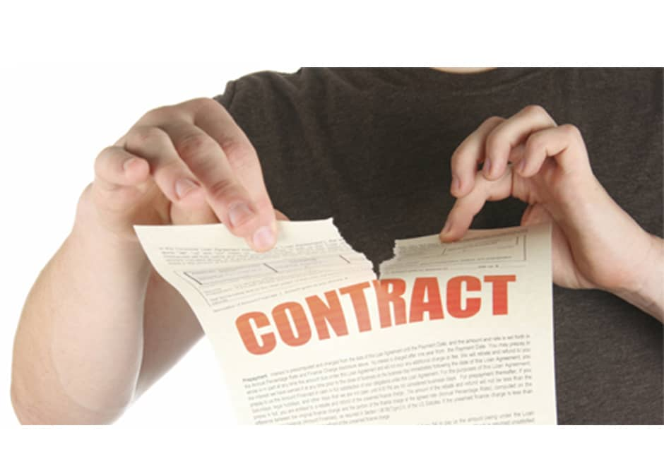 person tearing apart contract paper