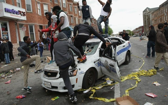 Riot jumping on police cars