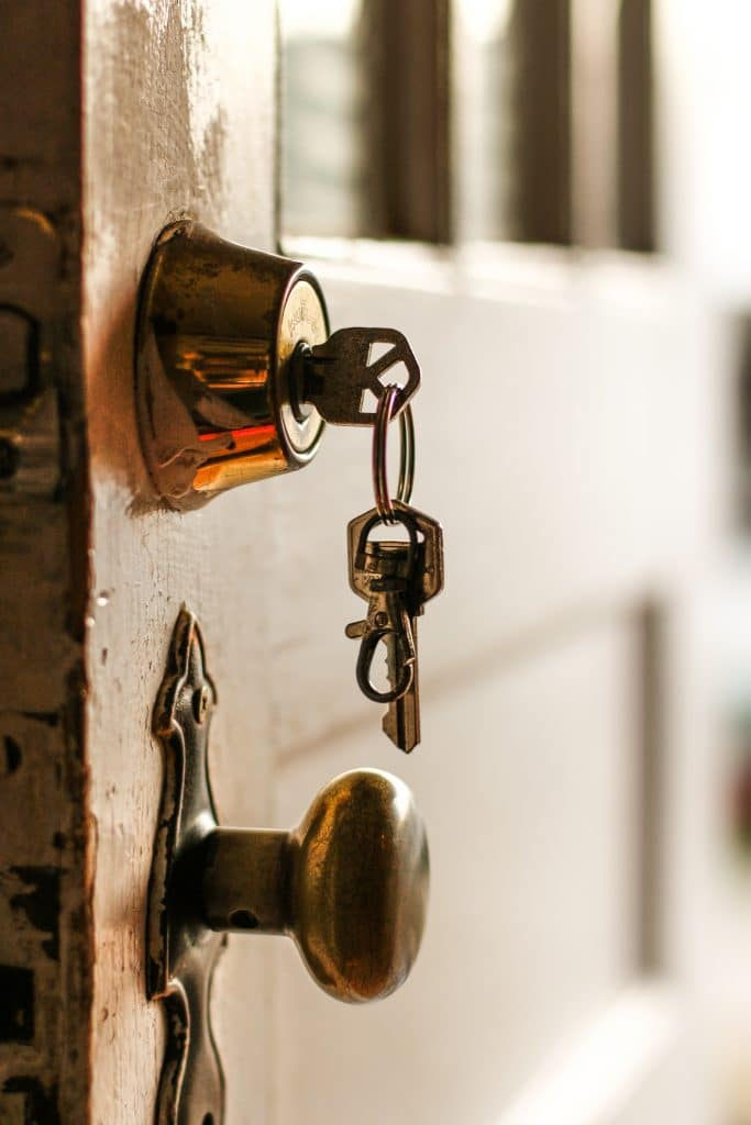 deadbolt lock installed on a door with its key inserted on it
