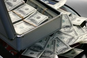 one hundred us dollar bills in a suitcase