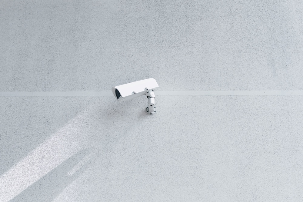 white security camera attached to the wall